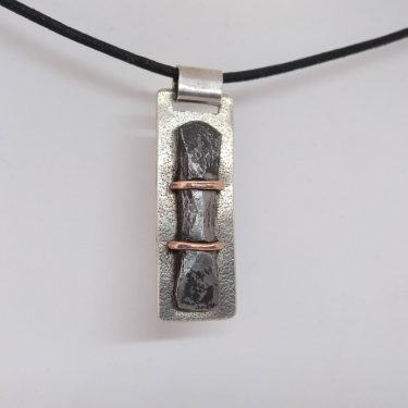 Silver pendant with iron and copper details.