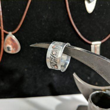 Anillo de plata con banda texturada y puntos de cobre